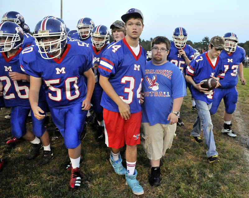 Trevor Perry, middle right, stands with the Messalonskee football team on the center of the field before hosting Skowhegan Area High School in Oakland friday night.