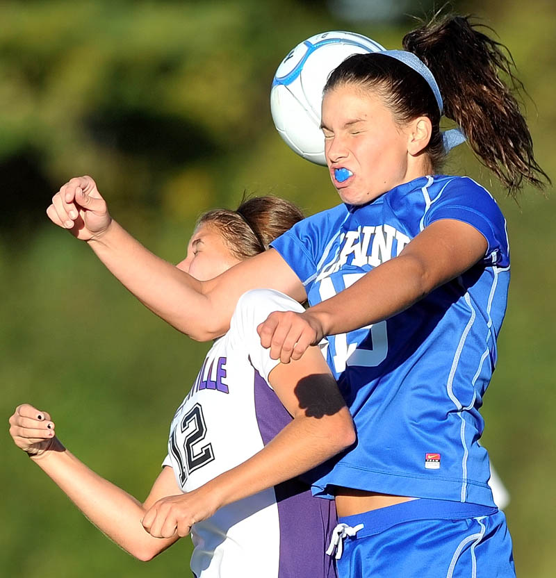 Staff photo by Michael G. Seamans Waterville Senior High School's Lydia Roy, 12, left, and erskine Academy's Bridget Humphrey, 15, right, battle for the header in double-overtime in Waterville Thursday. The game ended 3-3 in double-overtime.