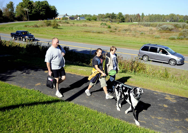 Staff photo by Andy Molloy NEW DIRECTION: Chris, left, and Stacey Shaw walk their son, Robert, 13, home Tuesday from Maranacook Community School in Readfield on the new sidewalk that connects the middle and high schools to the town hall in Readfield along Route 17.