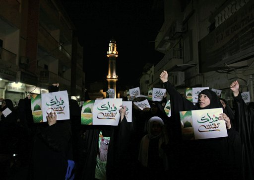 """Bahraini women chant outside a religious community center in Sanabis, Bahrain, as they listen to top Shiite cleric Sheik Isa Qassim speak Thursday, about a film made in the United States that sparked violence against U.S. embassies in Egypt, Libya and Yemen. Qassim, whose speech was projected on monitors to overflow crowds outside, urged Western nations to stop extremists from insulting Islam's Prophet Muhammad, saying freedom of expression should not include insulting other faiths. The signs read: """"We sacrifice ourselves,"""" referring to Prophet Muhammad."""