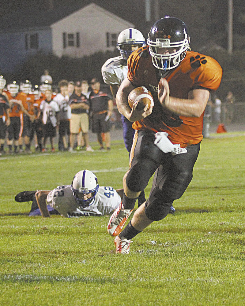 Photo by Jeff Pouland FINDING THE ENDZONE: Gardiner Area High School's Seth Wing scampers into the endzone for a first-half touchdown during Friday's night's game in Gardiner against Morse High School. Looking on is Morse High School's Scott Peterson (42) and D'Vaughn Myers (1).