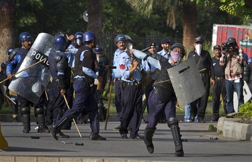 A Pakistani police officer throws a stone as others prepare to fire tear gas at protesters during clashes that erupted near the U.S. Embassy in Islamabad, Pakistan on Friday.
