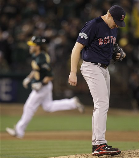 Boston Red Sox's Mark Melancon, right, turns his back as Oakland Athletics' Josh Reddick runs the bases, left, after Reddick hit a grand slam in the seventh inning of a baseball game Friday, Aug. 31, 2012, in Oakland, Calif. (AP Photo/Ben Margot)