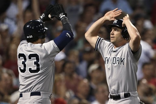 New York Yankees' Steve Pearce, right, is congratulated by Nick Swisher after scoring on a single by Derek Jeter in the seventh inning against the Boston Red Sox in a baseball game, Thursday, Sept. 13, 2012, at Fenway Park in Boston. (AP Photo/Charles Krupa)