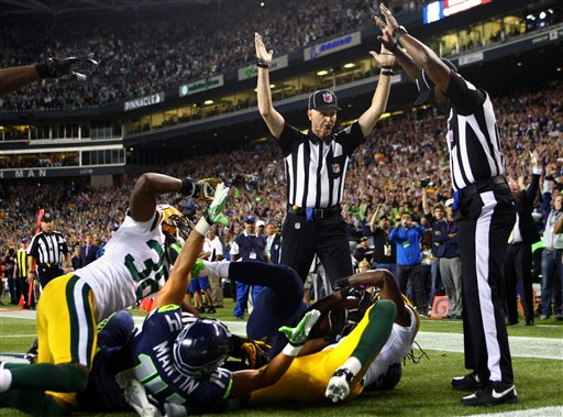 Officials signal after Seattle Seahawks wide receiver Golden Tate pulled in a last-second pass for a touchdown from quarterback Russell Wilson to defeat the Green Bay Packers 14-12 in an NFL football game, Monday, Sept. 24, 2012, in Seattle. The touchdown call stood after review. (AP Photo/seattlepi.com, Joshua Trujillo) MAGS OUT; NO SALES; SEATTLE TIMES OUT; TV OUT; MANDATORY CREDIT