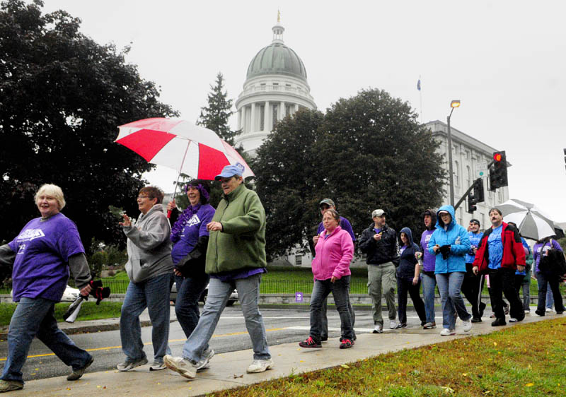 Some of the about 200 participants walk past The State House during the Alzheimer's Association Walk to End Alzheimer's on Saturday morning in Augusta. They walked a 2.8 mile course that started at Buker Center headed down Western Avenue, over to and around Capital Park and back up the Capital Street to the starting point.