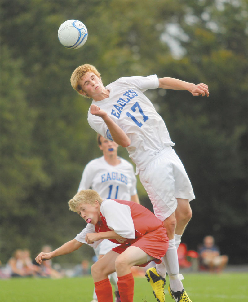 LOOK OUT BELOW: Erskine Academy's Tyler Adams lands on Cony High School's Connor Perry after going up for a header during the second half of Saturday's game in South China.