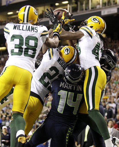 Green Bay Packers cornerbacks Tramon Williams (38) and Charles Woodson (21) and safety M.D. Jennings (43) fight for possession of a jump ball with Seattle Seahawks wide receivers Charly Martin (14) and Golden Tate, right, in the final seconds of the fourth quarter of an NFL football game, Monday, Sept. 24, 2012, in Seattle. Tate was ruled to have come down with the ball for a touchdown, and the Seahawks won 14-12. (AP Photo/Stephen Brashear) NFLACTION12;