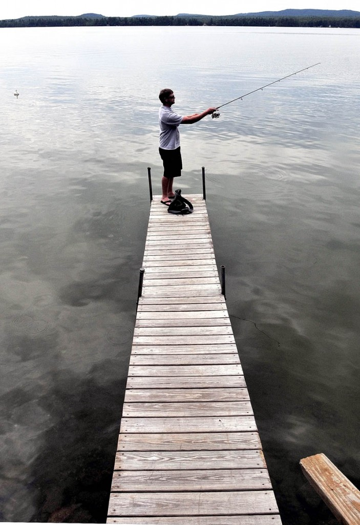 Standing at the end of a long dock, Dan Villwock casts his homemade lure in July 2010 while fishing for bass in North Pond in Smithfield, which is a part of the Belgrade Lakes Watershed.