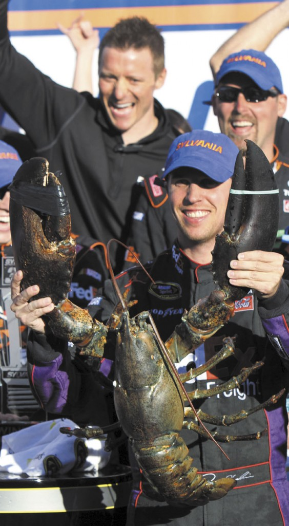 QUITE A PRIZE: Denny Hamlin holds up a lobster in victory lane after winning the NASCAR Sprint Cup race Sunday at New Hampshire Motor Speedway in Loudon, N.H.