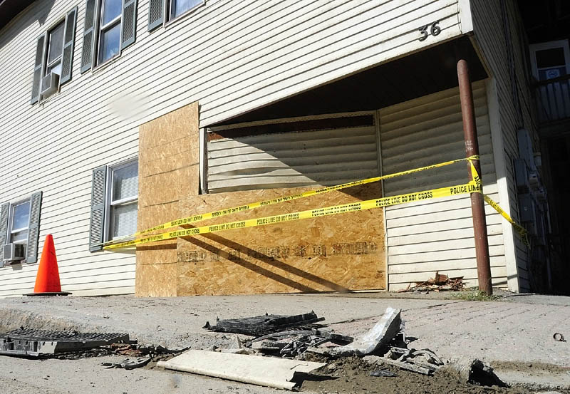 Plywood covers a hole in the wall on Saturday of 36 Water Street where a vehicle drove into Jim Pinkham's apartment on Friday evening. The orange cone, at left, covers the base of where a streetlight used to stand. Bits of streetlight and the vehicle are still on curb.