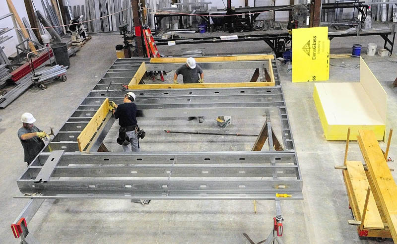 Workers build exterior wall panels for the new MaineGeneral regional hospital last week at the Porter Panel & Truss in Portland. The sections are build there, transported to Augusta and lifted into place by crane.