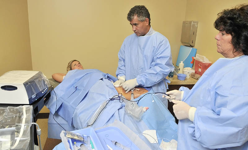 Dr. Chris Alvarado, center, and nurse Kim Gallant, right, perform a Venefit procedure on Vickie Hunnewell to treat chronic venous insufficiency recently in Manchester.
