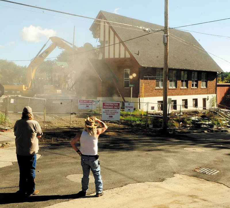 John Cash, left, and Jay Rice watch as excavators tear down the Augusta Spiritualist Church, at the corner of Court and Perham streets, Thursday morning to make way for the expansion of Kennebec County court complex.