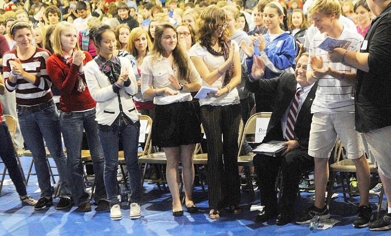 Staff photo by Joe Phelan Gov. Paul LePage, seated right, high fives Kat Newcombe while he receives a standing ovation following his speech on Wednesday afternoon at Erskine Academy in China. Gov. LePage spoke about domestic abuse and violence.