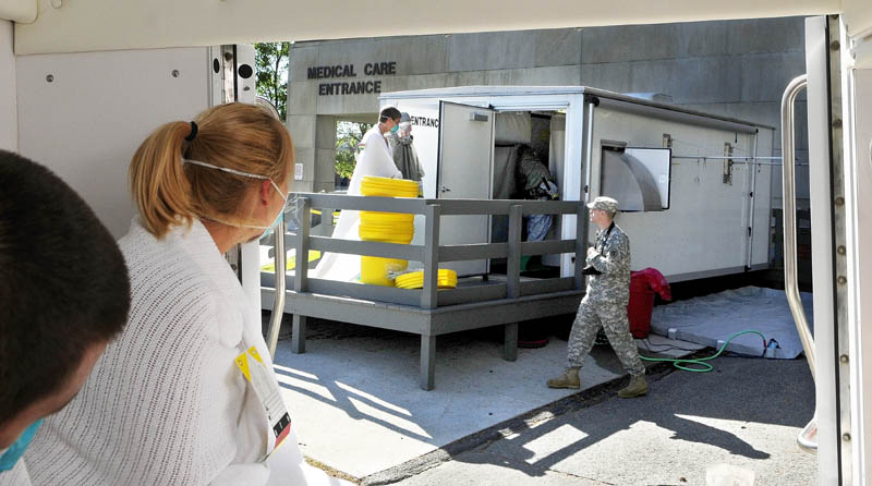 "Staff photo by Joe Phelan A Togus VA Medical Center staffer in a suit , center, leads a person playing a victim exposed to anthrax into the decontamination shed as another ""victim"" watches from inside an ambulance during a full scale joint Mass Casualty exercise on Tuesday at the Togus VA Medical Center. Five students from the Capital Area Technical Center Law Enforcement program went through the decontamination shed as part of the exercise."