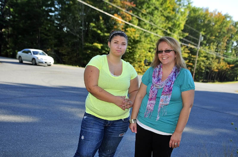 Emily Cote, left, and her mother Malinda Caron stand at the intersection of the North Hunts Meadow and Cooper Roads on Friday afternoon. It used to be the bus stop where last year Cote caught the bus from Whitefield to Cony High School.