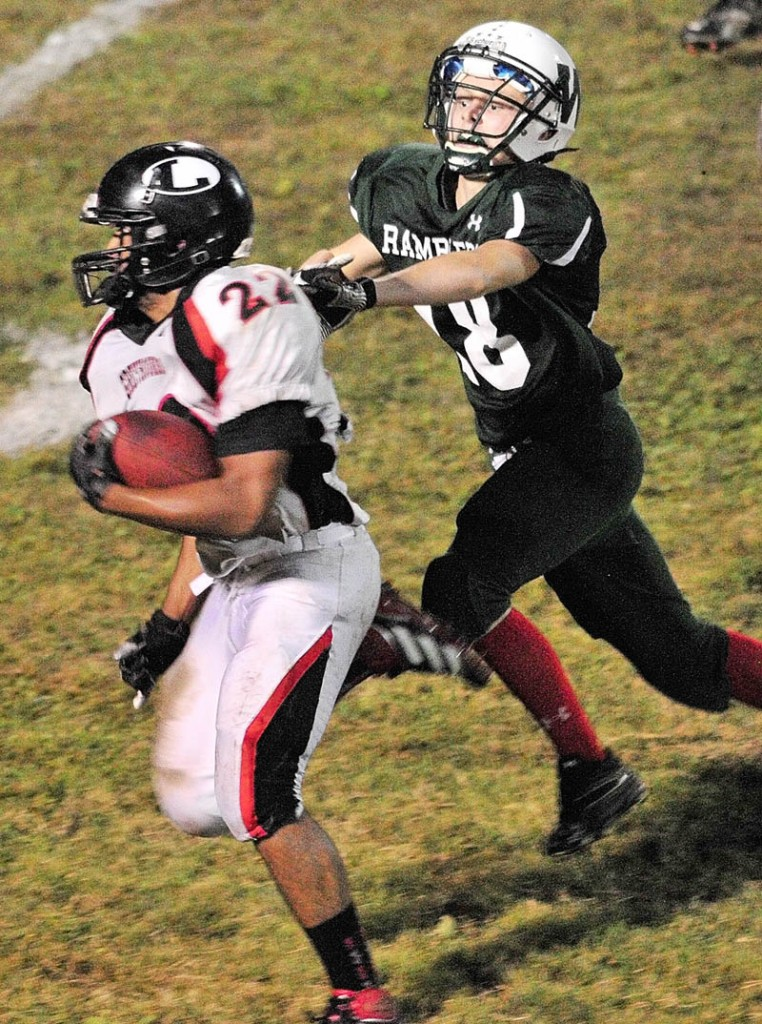 Staff photo by Joe Phelan Lisbon running back Quincy Thompson, left, out runs Winthrop lineback Zach Phinney during a game on Friday night at Maxwell Field in Winthrop.