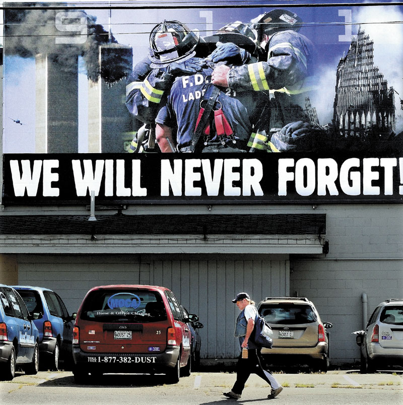 A pedestrian walks under a large mural in Waterville of firefighters embracing as the Twin Towers collapse in New York after terrorists attacked on Sept. 11, 2001.
