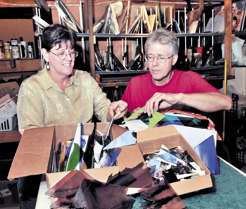 Staff photo by David Leaming SHARP: Lucy Boucher and Bernie Huebner pack boxes with scrap glass left from glass artwork made at their Stone Ridge Glass studio in Waterville. The couple are offering four-pounds of scrap glass to artists who will then make artwork for an exhibit at the Stained Glass Express on Oct. 20.