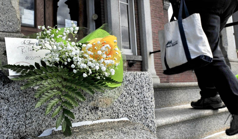 People walk into the Somerset County Superior Court in Skowhegan on Monday past flowers left in memory of Rita St. Peter who was killed 32 years ago. Jay Mercier has been charged in the murder and is on trial this week.