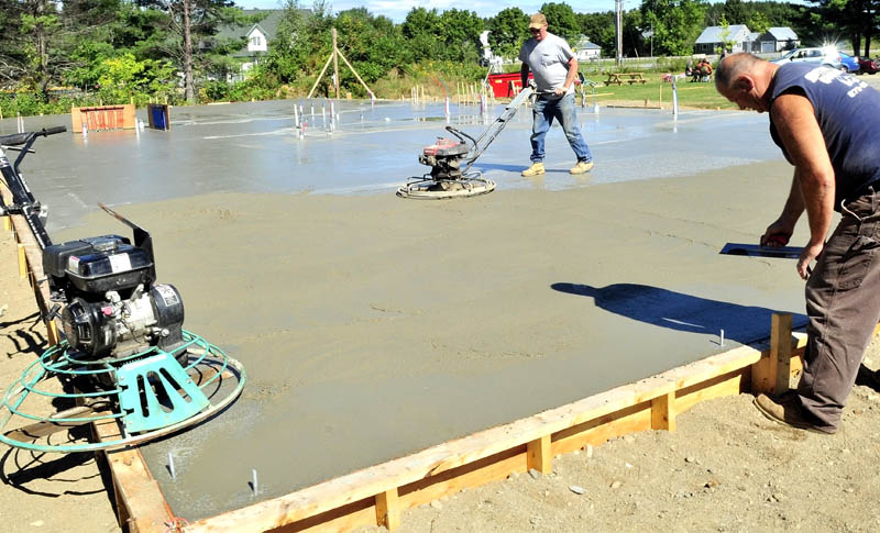 FOUNDATION: Dan Ellis, left, and Larry Hotham of Hotham concrete smooth the new foundation that was poured on Wednesday for the New Hope Women's Shelter in Solon.