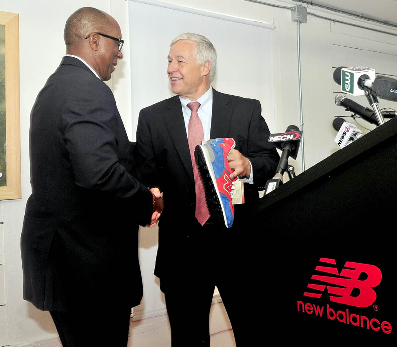RUNNING: U.S. Rep. Mike Michaud, right, gives U.S. Trade Representative Ambassador Ron Kirk a pair of New Balance shoe company sneakers on behalf of the company during a tour of the facility in Norridgewock on Thursday.