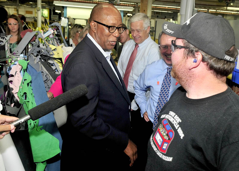 TRADE: U.S. Trade Representative Ambassador Ron Kirk speaks with New Balance employee Jeff Clair during a tour in Norridgewock on Thursday. U.S. Rep. Mike Michaud, center, also toured the company.