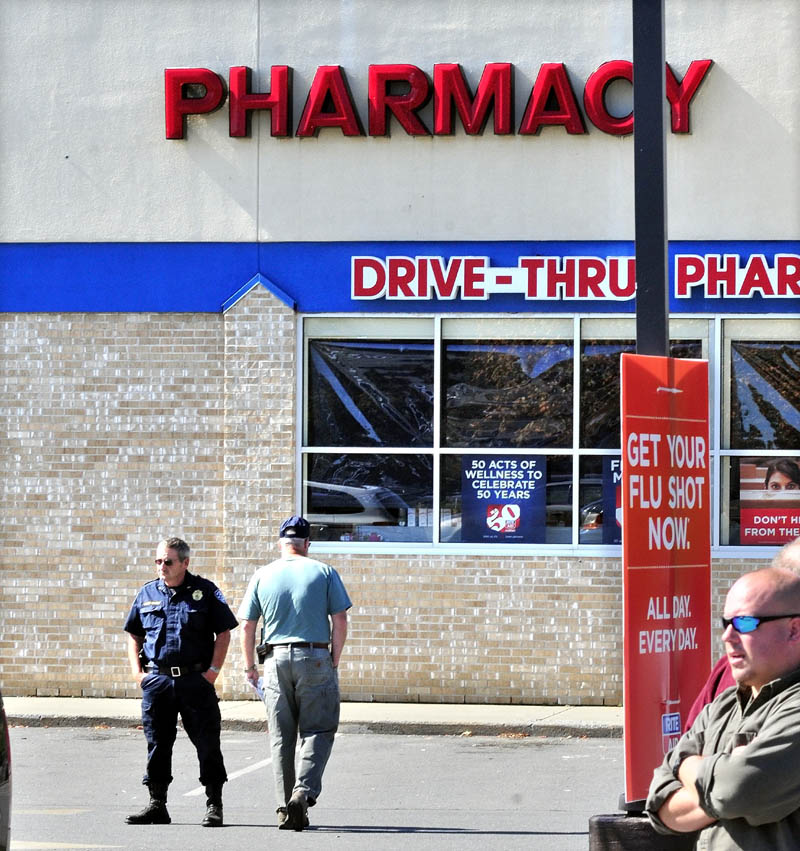 SECOND TIME: Pittsfield Police Chief Steven Emery, left, and officer Tim Roussin outside the RiteAid store in Pittsfield on Tuesday shortly after a male suspect handed a note to an employee demanding drugs. The suspect left the store without drugs and did not reveal the gun that he claimed he had.