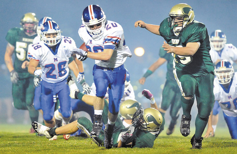 BREAKING AWAY: Messalonskee running back Corey McKenzie, center, breaks away from Oxford Hills defender Nick Bowie, back center, in the first quarter Friday night in South Paris.