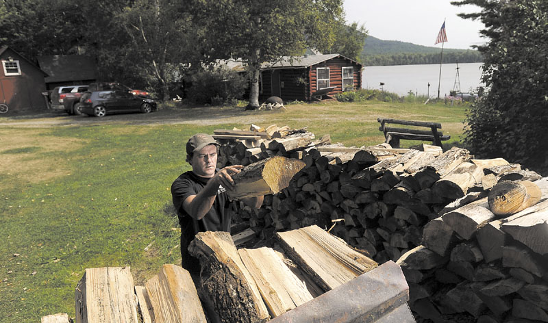 Dana Black moves wood into a bucket loader at Spencer Pond Camps, Friday. In addition to running the camps with his wife, Christine Howe, Black is also a lobsterman in Blue Hill.