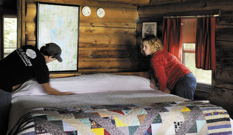 Dana Black and Christine Howe prepare one of the seven cabins they operate at Spencer Pond Camps on Friday. Both Black and Howe work full-time jobs in addition to owning and operating the camps.