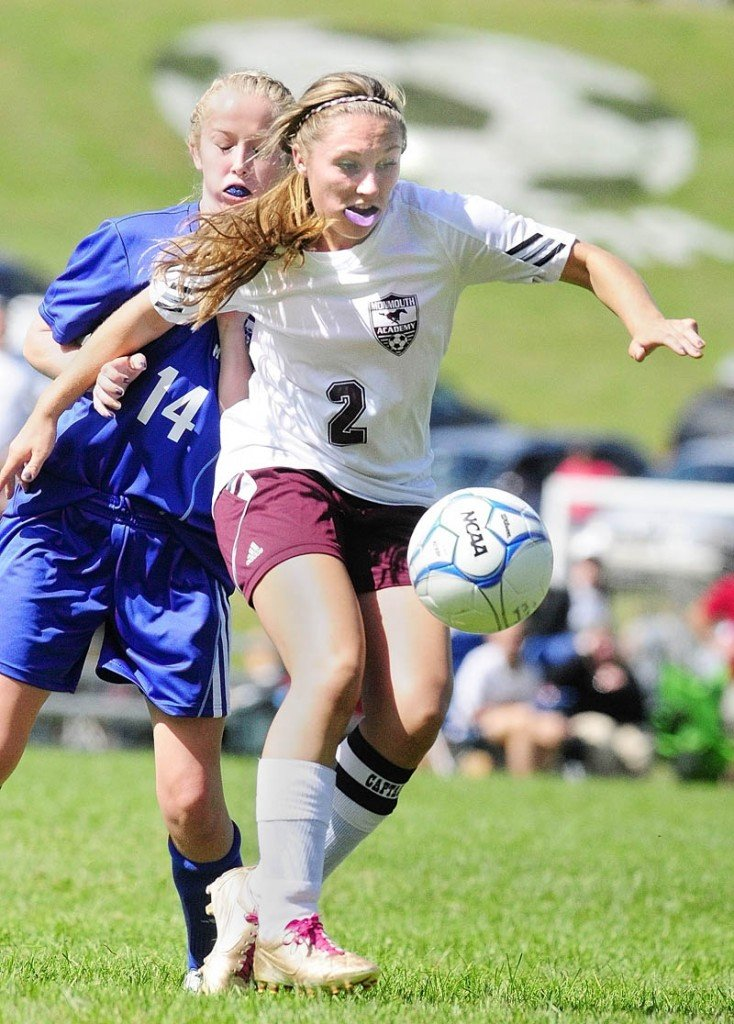LOOSE BALL: Mt. Abram's Alex Harnden, left, and Monmouth Academy's Danielle Bumann go for a loose ball during a girls soccer game Saturday at Monmouth Academy. Monmouth scored with seven seconds left in the second overtime to win 1-0.