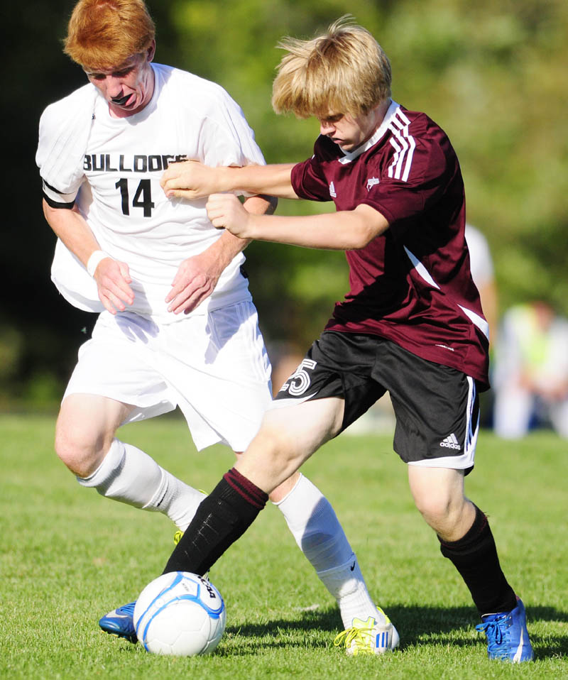 FIGHTING FOR POSSESSION: Hall-Dale's Colin Lush, left, and Monmouth Academy's Josh Reny go after a loose ball during a game Thursday afternoon at Hall-Dale High School in Farmingdale. The Bulldogs won 7-1.