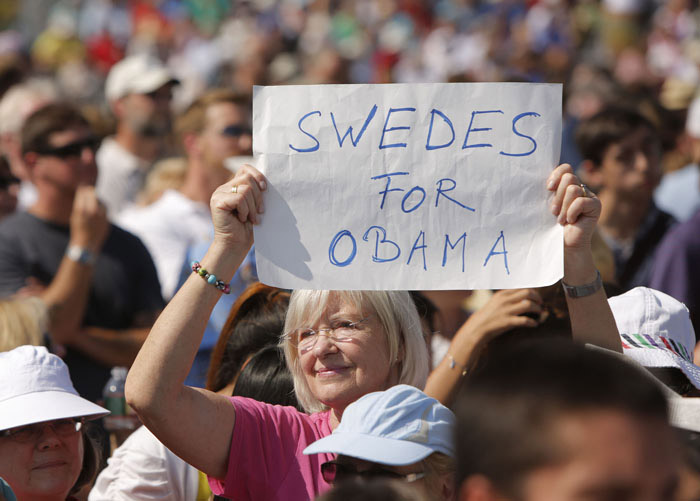 "A woman holds a ""Swedes for Obama"" sign in a field at the Strawbery Banke Museum in Portsmouth, N.H., hours before the scheduled arrival of President Obama, first lady Michelle, Vice President Joe Biden and Jill Biden."