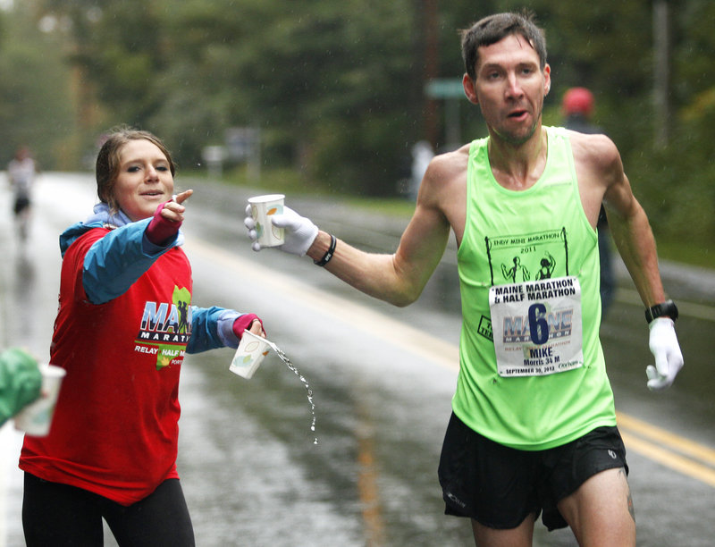 Mike Morris of Terre Haute, Ind., receives a cup of water from Sarah Kurland, a race volunteer from the Greely High cross country team, at a water station on Route 88 in Cumberland.