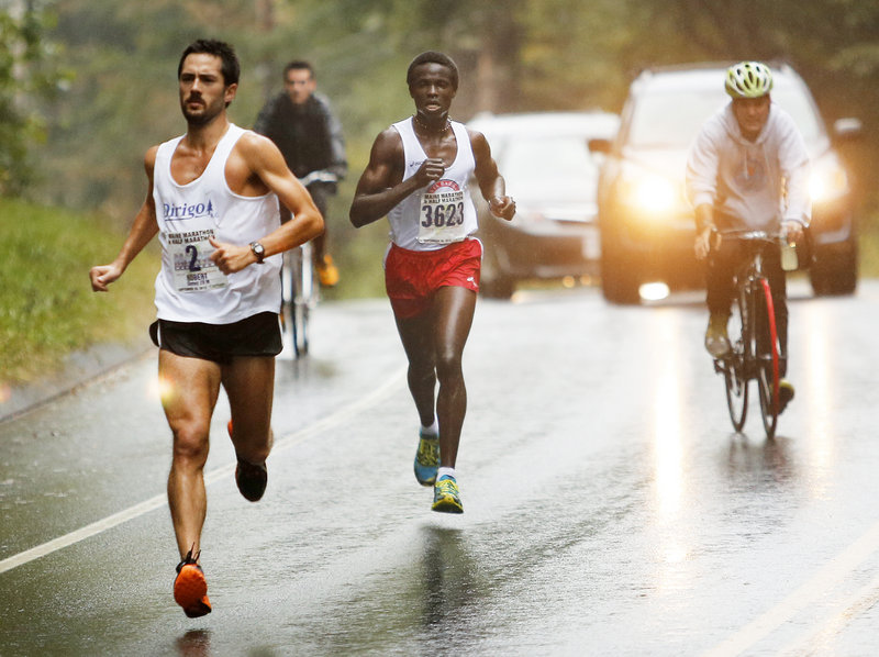 Robert Gomez of Saco, front, and Moninda Marube of Auburn approach the 10-mile mark during Maine Marathon on Sunday along Route 88 in Cumberland. While Gomez broke Vassallo's previous record, he didn't beat Vassallo.