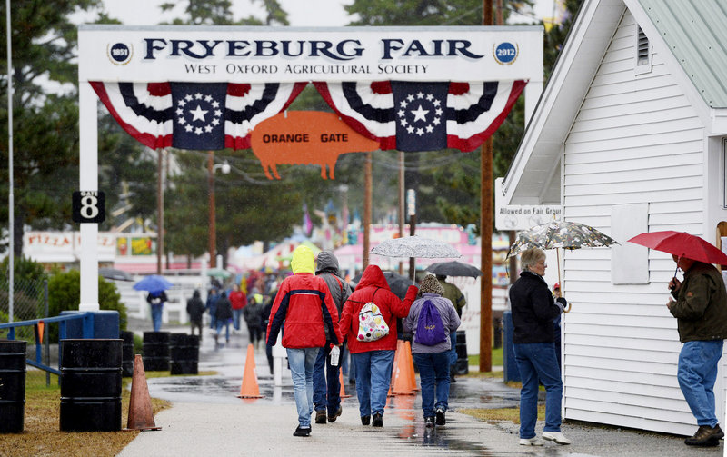 Fairgoers break out umbrellas as they make their way into the Fryeburg Fair on Sunday.