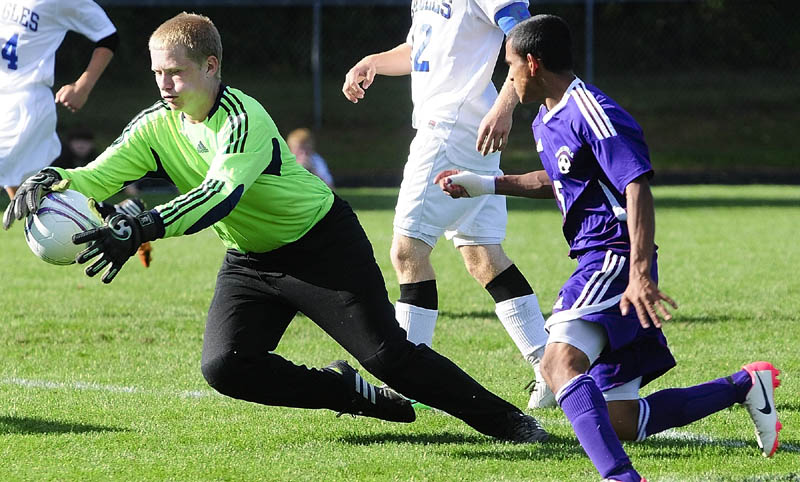 STOP THAT BALL: Erskine Academy keeper Jared Gartley, left, makes a save in front of Waterville's Denilo Guthro during a game Thursday at Erskine Academy in South China.