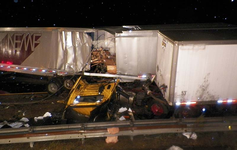 Two tractor-trailer trucks lie in the median of Interstate 95 in Biddeford on Friday night after they collided.