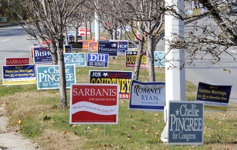 Dozens of political signs line the median along the approach to the Casco Bay Bridge in South Portland on Friday. Local sign makers say simple is best, and the fewer words, the better.