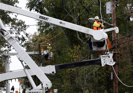 FILE - This photo taken Oct. 30, 2012, shows a utility crew working on damaged power lines in the aftermath of superstorm Sandy in Berlin, Md. One week before a close election, superstorm Sandy has confounded the presidential race, halting early voting in many areas, forcing both candidates to suspend campaigning and leading many to ponder whether the election might be postponed. It could take days to restore electricity to all of the more than 8 million homes and businesses that lost power when the storm pummeled the East Coast. That means it�s possible that power could still be out in some states on Election Day _ a major problem for areas that rely on electronic voting machines. (AP Photo/Alex Brandon)