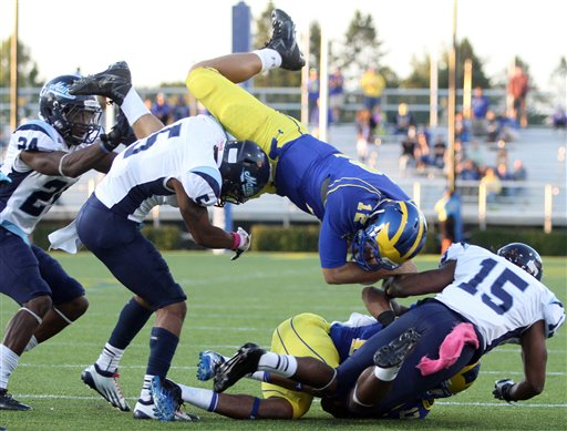 Maine defensive backs, from left, Khari Al-Mateen, Kendall James and Jamal Clay upend Delaware quarterback Trent Hurley, forcing a fumble in the fourth quarter of an NCAA college football game at Delaware Stadium in Newark, Del., Saturday, Oct. 6, 2012. (AP Photo/The News Journal, William Bretzger) NO SALES MAINE 26;UD 3