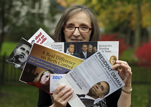 "Jean Gianfagna displays some of the political mailers her family receives at her home in Westlake, Ohio. Gianfagna says her family is ""deluged"" and sometimes gets four of the same piece at a time – her husband and two grown kids all get their own. Voters in battleground states have been inundated by mailers, calls and visits to their homes."