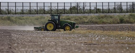 A tractor works a cotton field along the border fence that passes through the property in Brownsville, Texas.