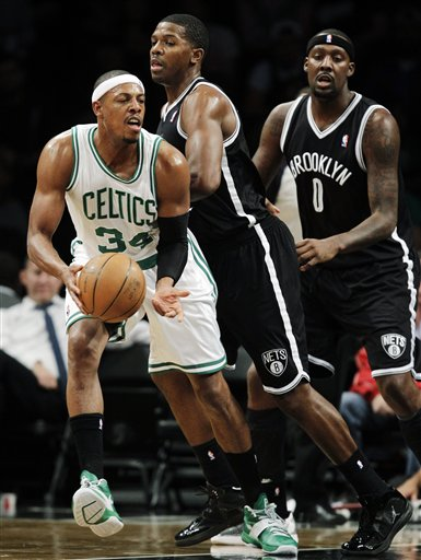 Boston Celtics forward Paul Pierce (34) passes the ball as Brooklyn Nets guard Joe Johnson (7) and forward Andray Blatche (0) defend in the first half of their preseason NBA basketball game at Barclays Center, Thursday, Oct. 18, 2012, in New York. (AP Photo/Kathy Willens)