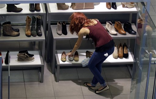 A clerk straightens up at a shoe store in Salem, N.H. Americans increased spending last month.