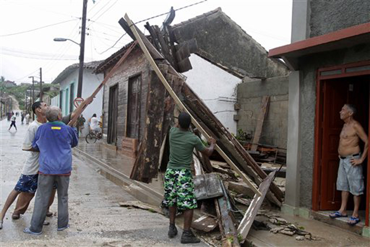 Men try to free an electrical wire after the passing of Hurricane Sandy in Gibara, Cuba, on Thursday. Power was turned off as the hurricane blasted across eastern Cuba as a potent Category 2 storm.