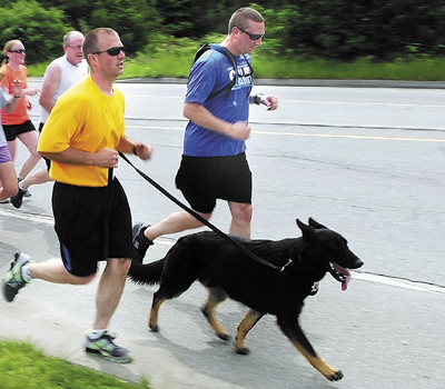 Waterville Police Officer Lincoln Ryder, far right, and Kennebec County Sheriff's Cpl. G.J. Neagle III, second from right, with Dracco, his police dog, lead a leg of the Special Olympics Torch Run through Winslow into Waterville on June 7, 2012.