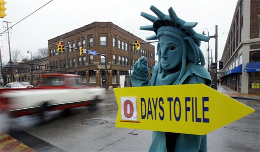 Max Martinez, dressed as the Statue of Liberty, tries to alert motorists on the final day to file taxes in this 2011 photo. A typical middle-income family making $40,000 to $64,000 a year could see its taxes go up by $2,000 in 2013 if lawmakers fail to renew a lengthy roster of tax cuts set to expire at the end of 2012, according to a new report.